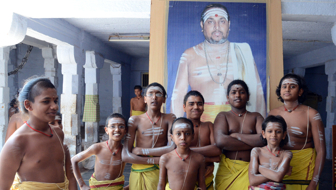 Student priests. Three lines of white indicate their affiliation with Shiva. The picture behind is their guru.