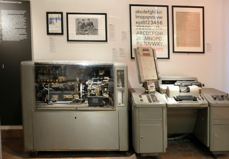 The Lumitype at the Museum of Printing with its interior workings revealed. The poster is a display of the font Univers.